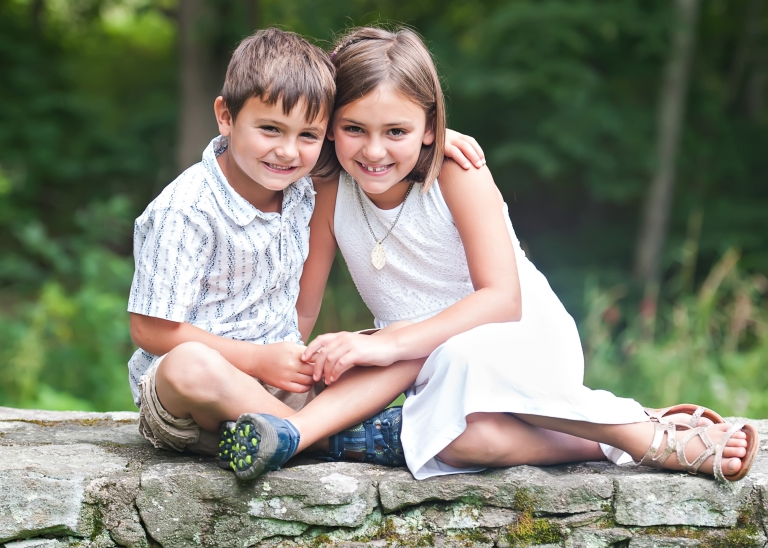 brother and sister sitting on stone wall