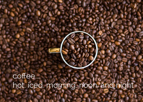 coffee cup filled with coffee beans surrounded by coffee beans