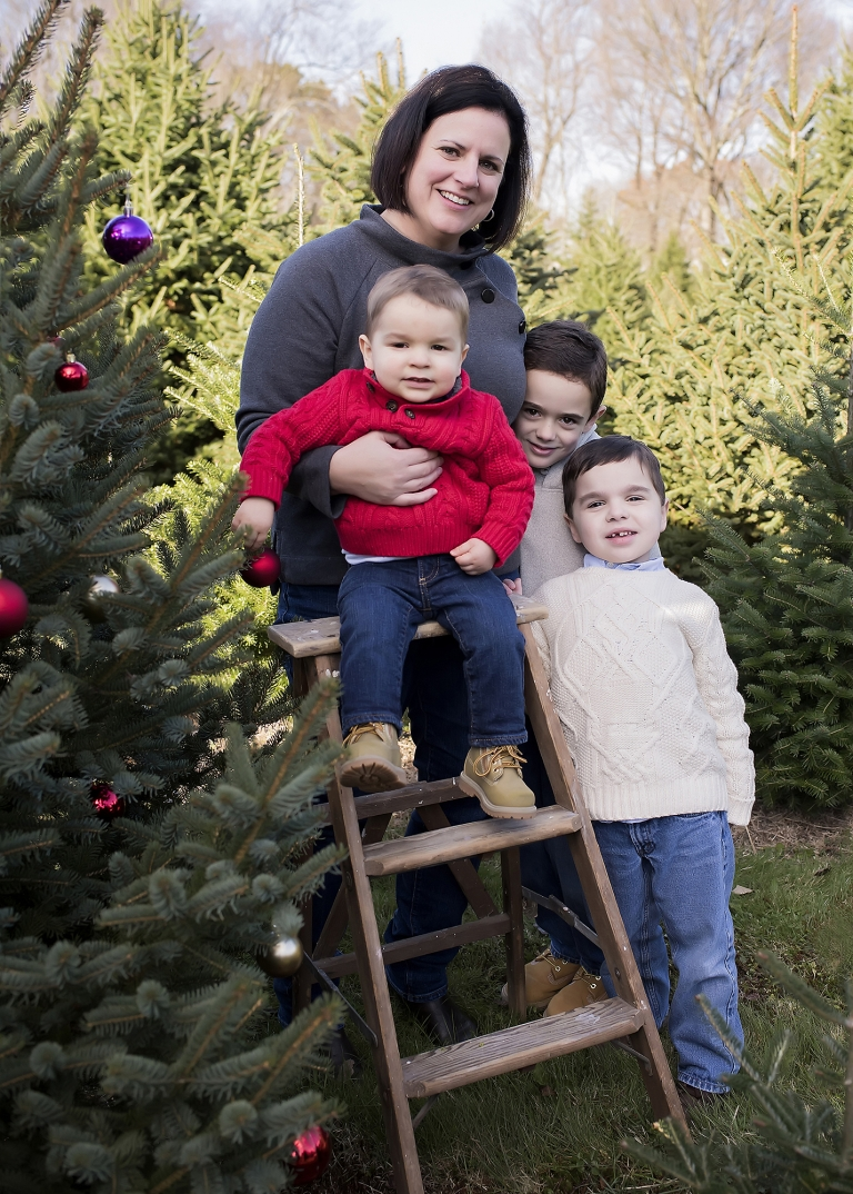 Mother standing with three young sons at christmas tree farm in North Attleboro MA